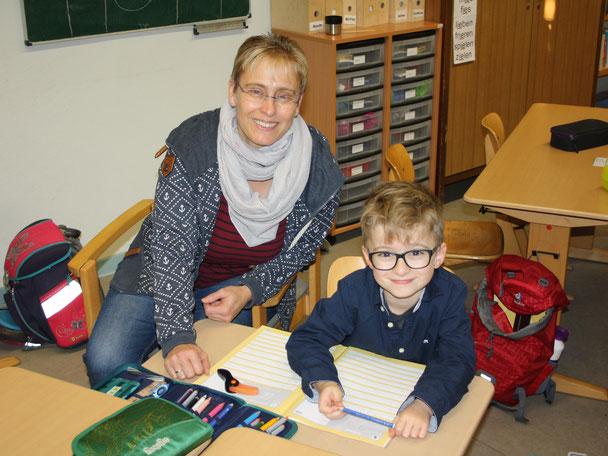 Das Foto zeigt einen Jungen und seine Schulbegleiterin. Foto: Oliver Hofmann