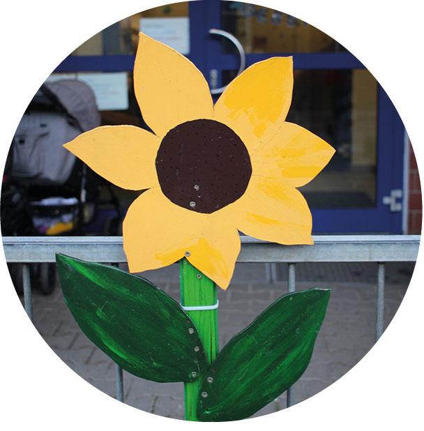 Eine Sonnenblume, aus Holz gebaut und bemalt, markiert den Eingang in die Kindertagesstätte Holweider Straße 62.