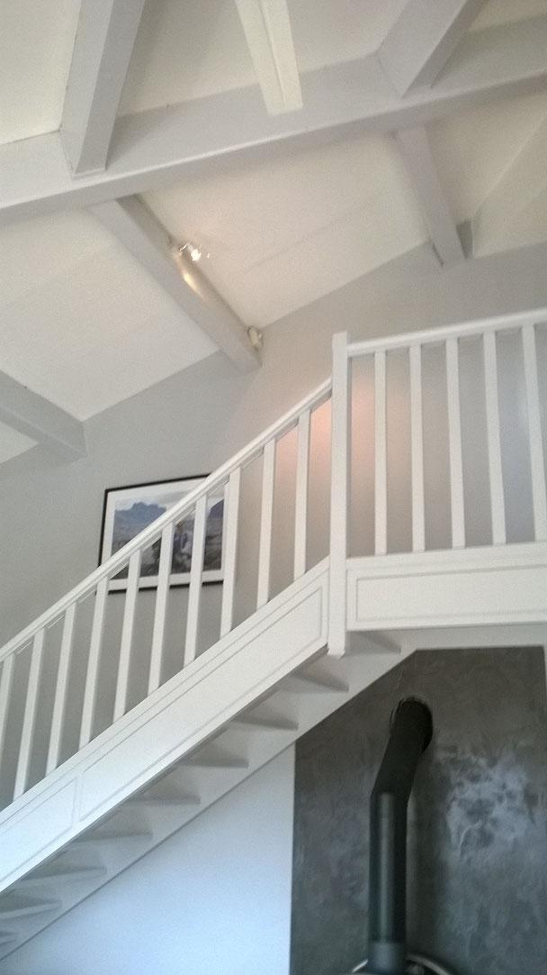 Après travaux. Peinture décorative des poutres, rambarde, escalier et murs. La paroi derrière le poêle est en béton ciré.