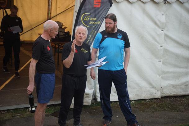 Rzben Loew (rechts) lauscht gespannt den fachkundigen Kommentaren eines Sportlers, während Cheforganisator Wolfgang Kownatka (links) sicherheitshalber schon mal die Rotweinflasche (vrmutlich Ahrwein) festhält.
