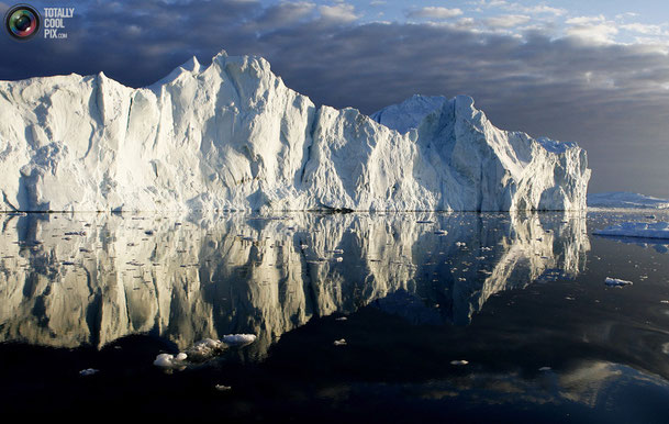 Айсберги, отражающиеся в спокойных водах в устье фьорда Jakobshavn вблизи Илулиссат. Фотография сделана 15 мая 2007 года.