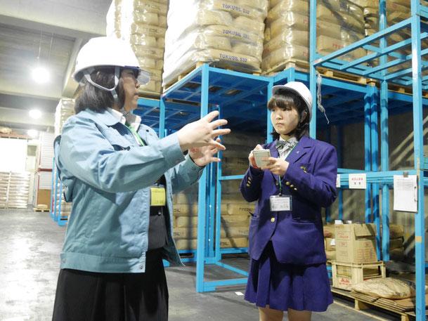 秋元運輸倉庫倉庫内において、説明を行う同社:上田さんとあおやまさん。朝日新聞に掲載された画像です。