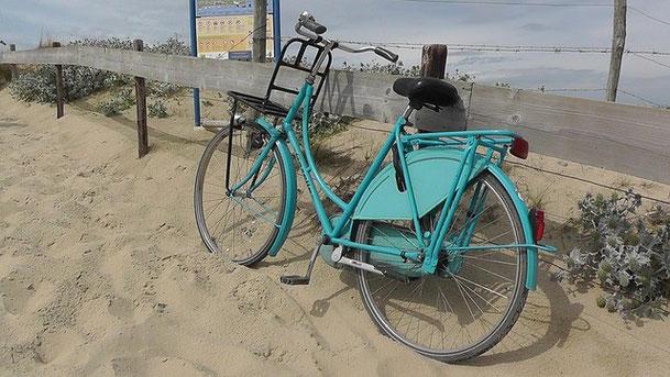 vélo hollandais bleu vert sur la plage