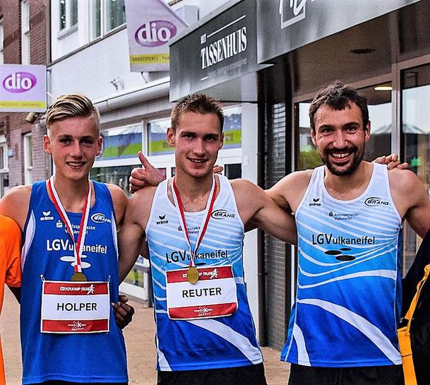 Tom Reuter, umreiht von seinen Teamkameraden Niclas Holper und Andreas Keil beim Straßenlauf im niederländischen Varsseveld