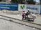 2 Welten - Familie zieht mit ihrem Transportmittel an Handywerbung vorbei