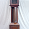 Angeliter Uhrengehäuse aus Mahagoni, bestehend aus dem geraden Sockelkasten, dem Mittelkasten mit gewölbter Tür und einem Uhrenkasten mit Säulen und Kranzverzierung.