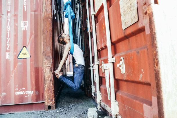Eine Frau macht Sport im Flying Pilates Tuch zwischen zwei Containern.