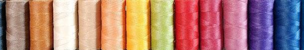 12 bobines de fils micro macramé alignées de couleurs différentes, donnant un effet multicolore