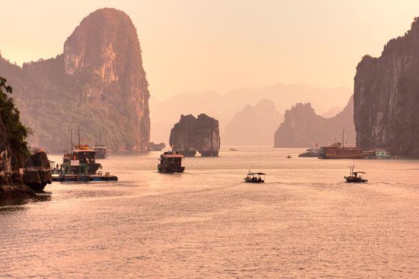 Blick auf die Vinh Ha Long Bucht mit Booten und Sonnenaufgang