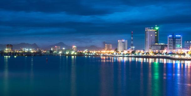 Blick vom Meer aus auf die abendlich beleuchtete Stadt Da Nang