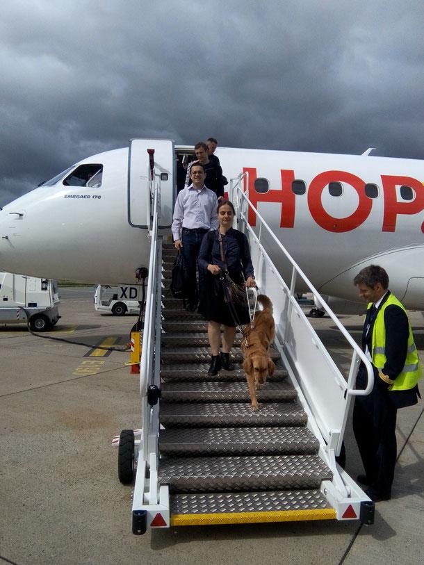 Personne déficiente visuelle descendant d'un avion guidée par son chien. Crédit : FFAC
