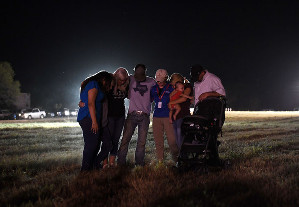 People pray at a vigil, after a mass shooting that killed 26 people in Sutherland Springs, Texas on November 6, 2017.