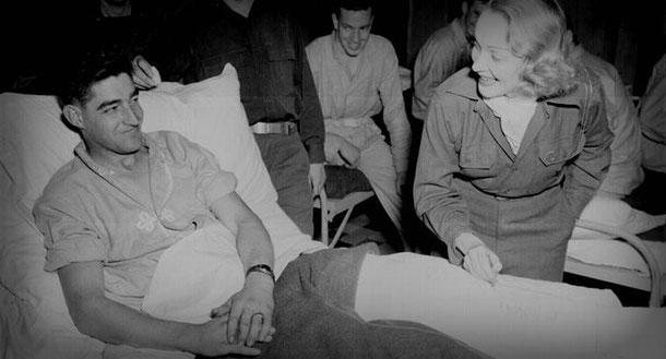 Marlene Dietrich spricht einem verwundeten US-Soldaten Mut zu. Lizenz: gemeinfrei