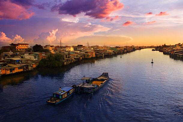 Ein Sonnenuntergang am Mekong Fluss mit Schiffen