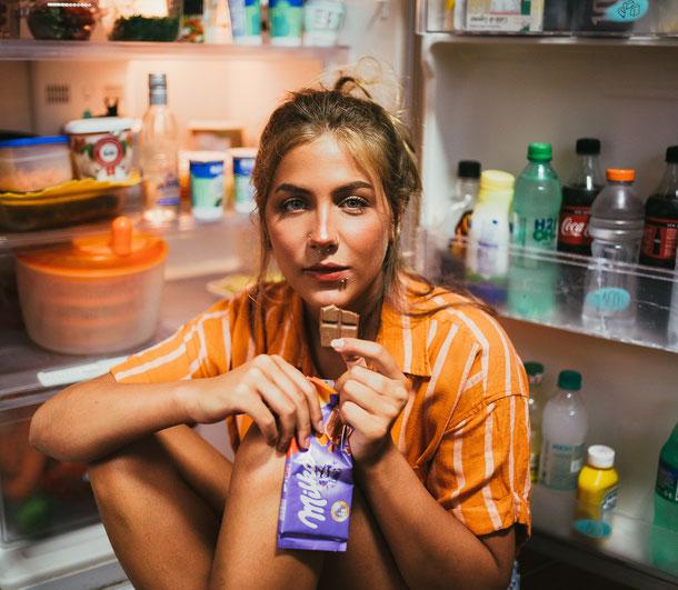 Jeune femme assise devant son réfrigérateur ouvert qui mange une tablette de chocolat.