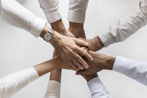 Hände die übereinander geschlagen das Team symbolisieren. Mit dem Coaching von A-Training wird auch ihr Teamerfolg gesteigert.
