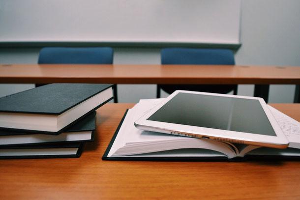 Ein Tablet auf einem Buch, was symbolisiert, was eigentlich Blended Learning ist. Die Verknüpfung von klassischen und modernen Lernmethoden. Effizient und Nachhaltig. nova-learning bietet dies in Reinkultur.