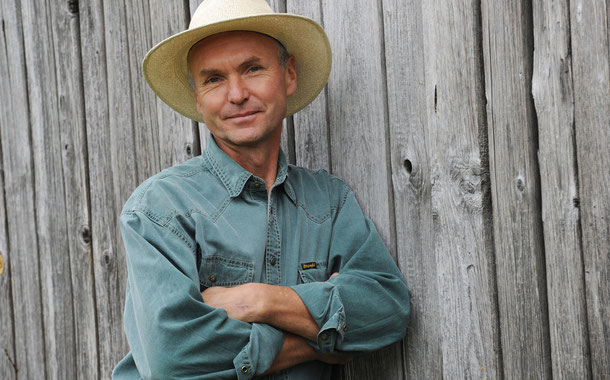 Bild: Heiko Schneider vor einer verwitterten Holzwand