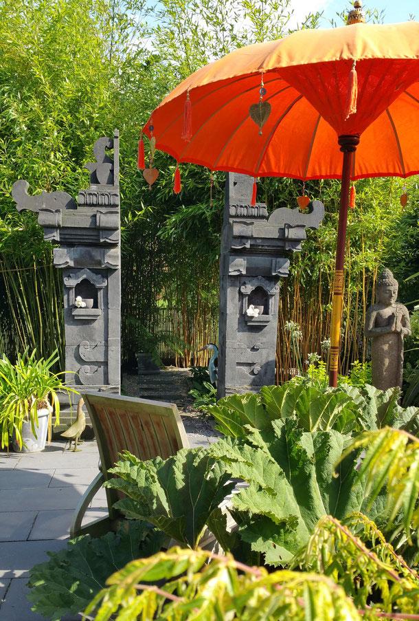 Neben dem Tempeltor steht ein Buddha mit Begrüßungsgeste, davor ein typischer Balischirm