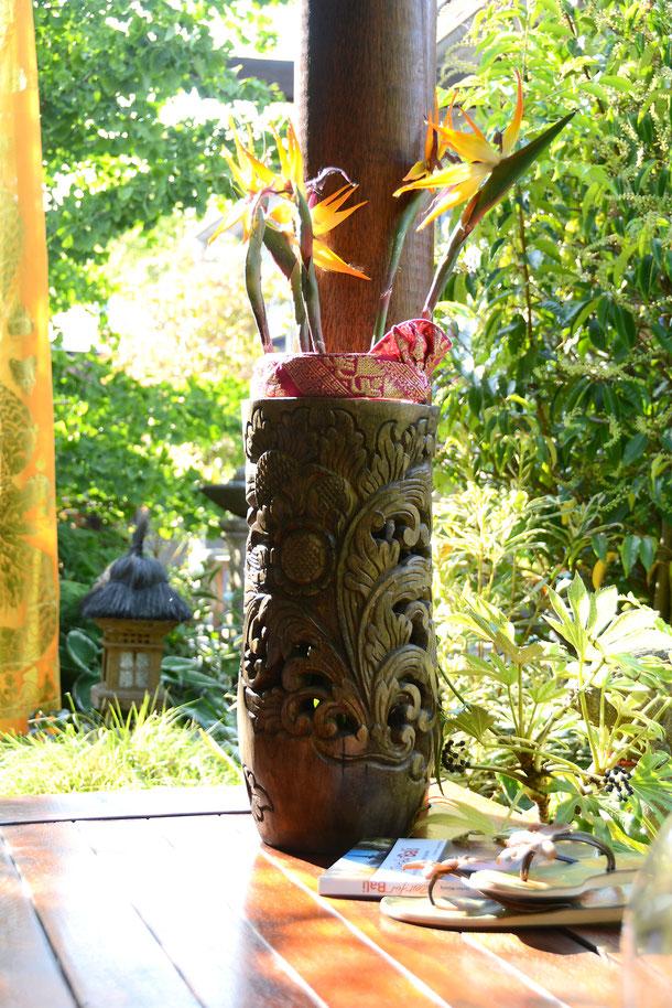 Detailreich geschnitzte Holzvase im Vordergrund; Bali-Laterne und -Fahne im Hintergrund