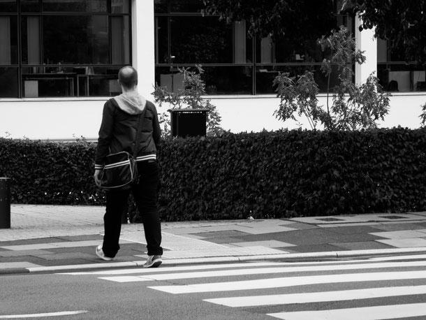 Mann mit gestreifter Tasche geht über Zebrastreifen, street, stripes, man with bag, monocrome, schwarz-weiss, Schwarzweissfotografie, kreative Fotografie, Fototipps
