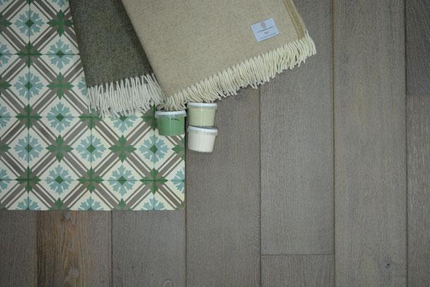 Geräucherter Eichenboden, grau geölt und Zementfliese N° 10700 und Schurwolldecke beige braun