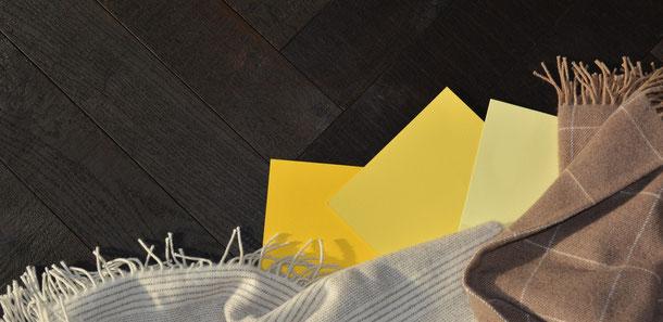 Kombinationsempfehlung schwarzes Parkett mit Gelbtönen und braun-beigen karierten Schurwolldecken