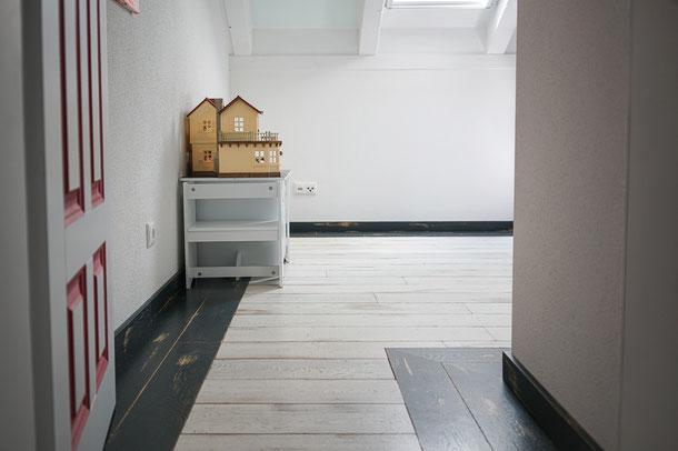 Schwarze Sockelleiste farblich abgestimmt auf den Vintage Dielenboden in weiß und schwarz