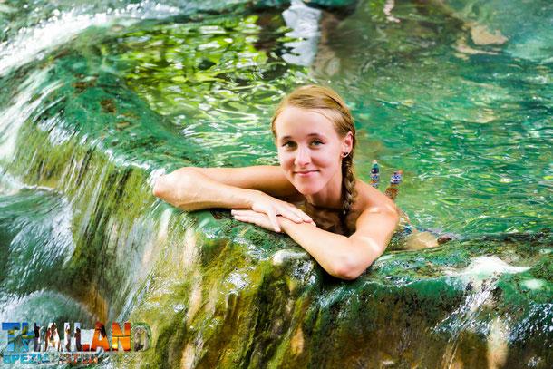 Frau liegt mit Bikini in einem Wasserfall Südthailands