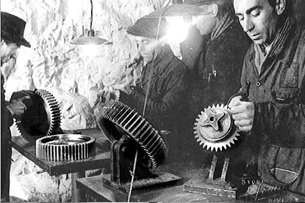 Operai FIAT in una fabbrica in galleria costruiscono ingranaggi del motore del ME109
