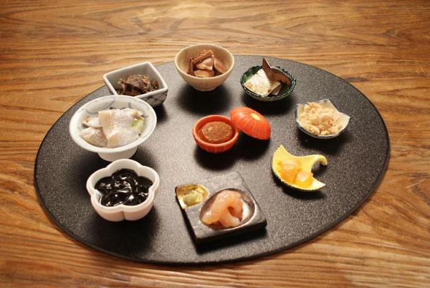 天たつの酒肴九品膳には、日本三大珍味の一つでバフンウニと塩だけで仕込んだ濃厚なウニの逸品「越前仕立て汐雲丹」、福井の漁港で取れた新鮮甘えびを昆布で締めた本当に甘い「甘えび昆布〆」、いか塩辛にイカスミを合わせたコクある塩辛「黒作り」、小鯛の切り身の甘酢〆「小鯛ささ漬」、一年樽で寝かせ熟成発酵させた濃厚な旨味と福井の酒粕の甘い香りかおる「へしこ酒あらい」など、福井らしいとても美味しいお酒の肴が9種入ります