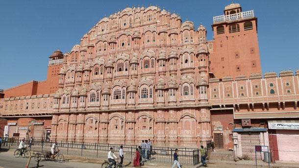 """Hawa Mahal oder """"Palast der Winde"""" wurde 1799 vom Dichterkönig Sawai Pratap Singh für die königl. Damen errichtet, damit diese die Prozessionen und Tag zu Tag Aktivitäten von der kühlen Ummauerung der majestätischen Fassade aus genießen konnten."""