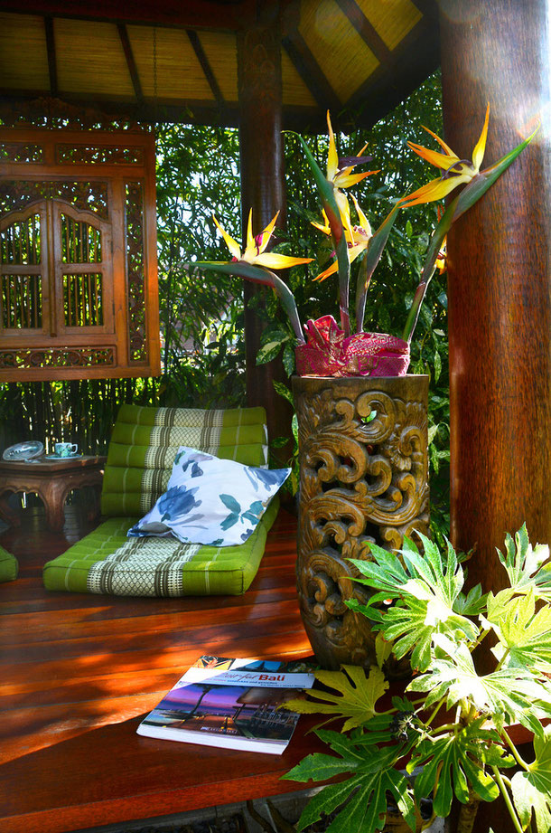 Balinesische Gazebo-Zutaten: schmückendes Holzrelief und -Vase, dazu eine frostfeste Fatsie