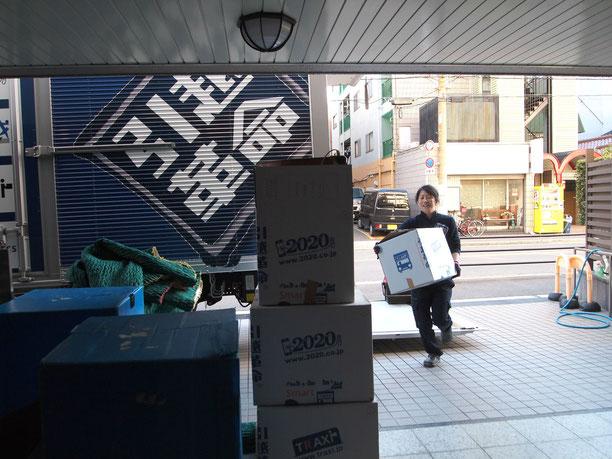 トラックから荷物を降ろして運ぶ姿