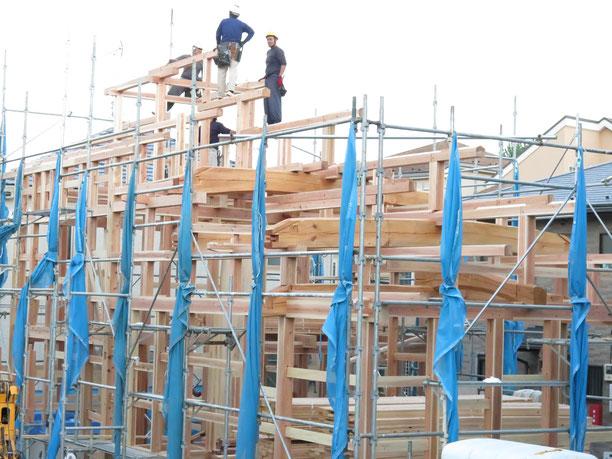 国産の無垢材を手刻みで加工し、大きな梁や大黒柱を組んで木組みの家を建てていく。建方を行う大工たちの写真
