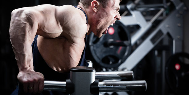 Ein Athlet mit starken Oberarmen strengt sich an