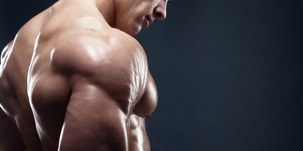 ein Mann steht im freien Oberkörper und zeigt seine breiten Schultern