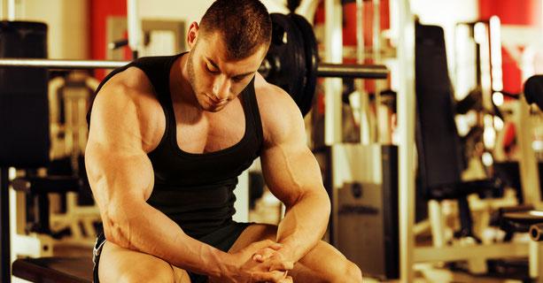muskulöser Athlet sitzt im Fitnessstudio auf einer Trainingsbank