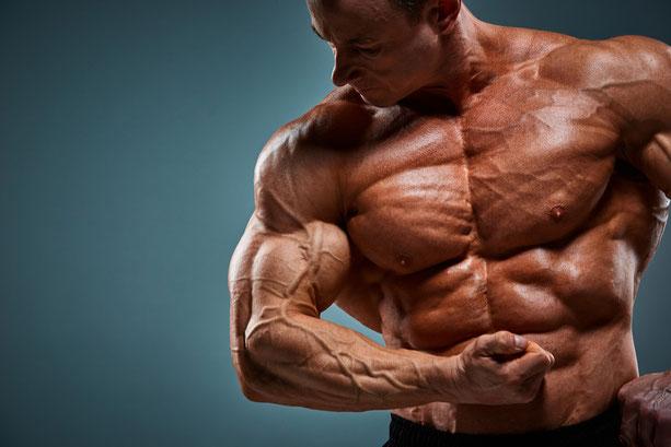 Muskelaufbau-Training - Mann spannt seine Oberarmmuskeln an