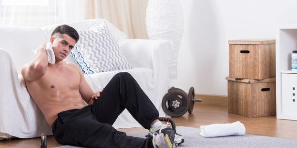 junger Mann mit starken Muskeln bei sich zu Hause