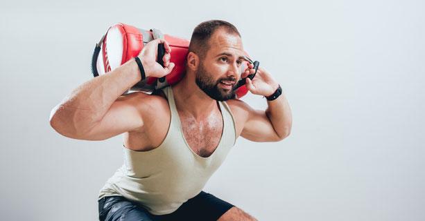 Mann trainiert Kniebeugen mit einem Gewichtssack auf dem Rücken