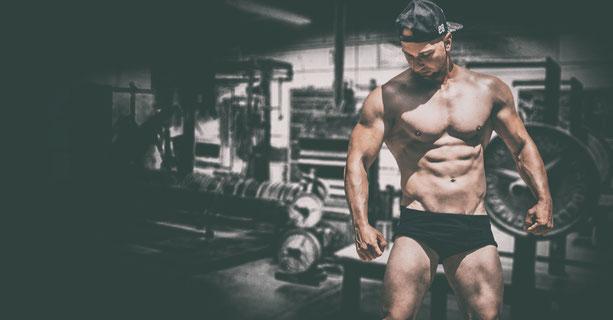 Bodybuilder im Fitnessstudio schaut auf seine Muskeln am Oberarm
