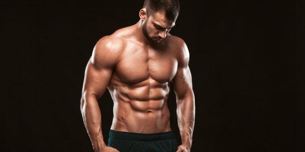 Sportlicher Mann mit freiem Oberkörper zeigt seine Bauchmuskeln