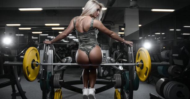 Eine hübsche, junge Frau sitzt auf einer Hantel im Fitnessstudio