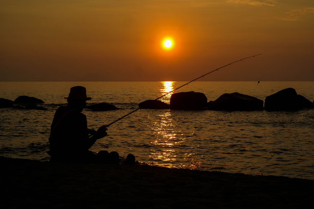 A fisherman on a beach in Italy in front of the sunset.