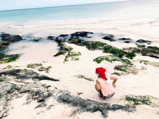 Kind mit Weihnachtsmütze am Strand.