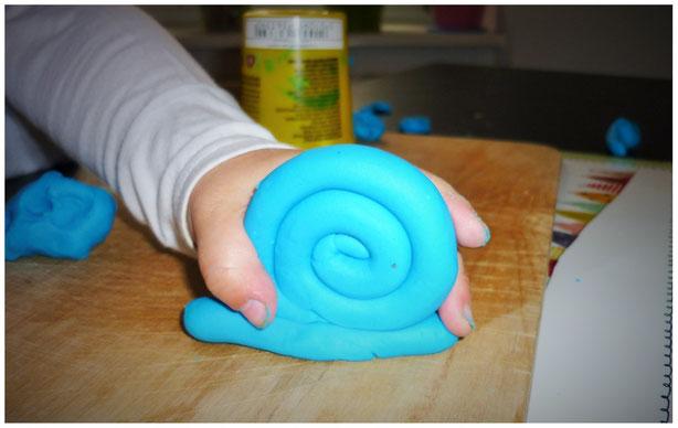 Kinderhand, die eine Schnecke aus blauer Knete hält