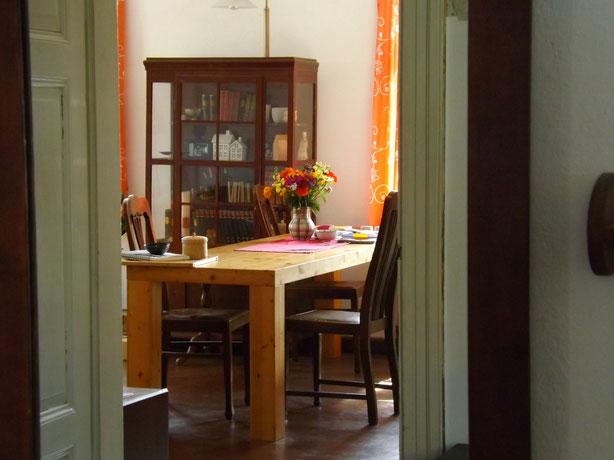 Spiegelbild des Wohnzimmertisches vom Flur aus  - die Monatscollage ist fotografierfertig aufgebaut.