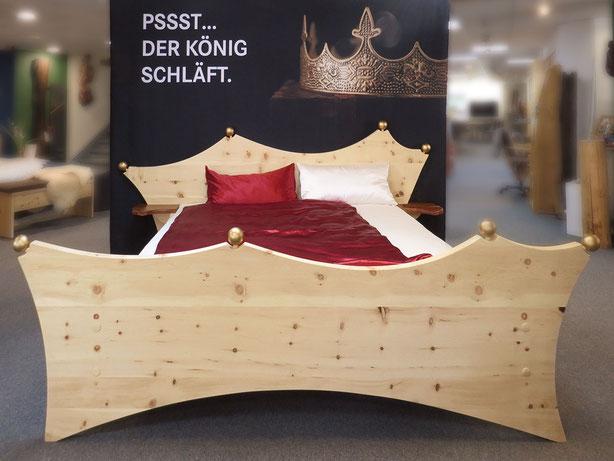 """Zirbenbett """"Königsbett, Kopf- und Fußteil in Kronenform mit goldenen Kugeln, Bett steht vor einer schwarzen Wand mit Spruch """"Pssst. Der König schläft"""" und Bild """"Krone"""""""