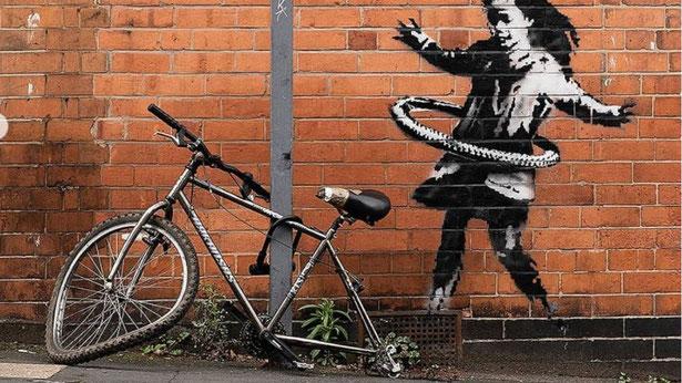 『自転車の車輪でフラフープをする少女』